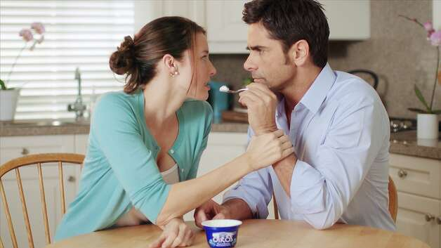 This advertisement provided by Dannon Co,. shows a scene from the Dannon Oikos Greek Yogurt Super Bowl commercial, starring Jessica Blackmore and John Stamos. The Dannon Oikos advertisement will run during the third quarter of Super Bowl XLVI, Sunday, Feb 5, 2012. About 20 of the roughly 36 Super Bowl advertisers put their TV commercials online in the days leading up to Sunday's broadcast. That's a big break with tradition and up from last year when only a handful of companies released their ads before the game. Stamos' Dannon ad is one of the ads that have been pre-released. (AP Photo/Dannon Co.) Photo: Associated Press
