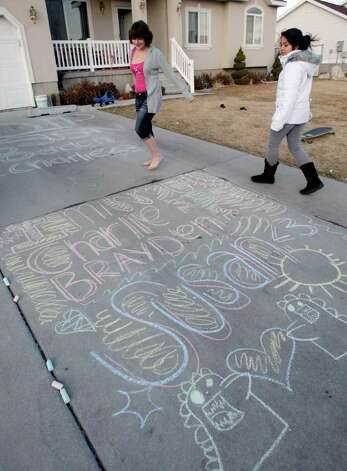Alexis and Mercedez Trujillo look at a chalk art memorial they created at their home in Salt Lake County, Utah  Sunday, Feb. 5, 2012. Days after a judge ruled against Josh Powell in a child custody hearing, Powell and his two young sons Charles and Braden were killed Sunday when police said he intentionally blew up a house with all three inside ó a tragic ending to a bizarre case that began more than two years ago when Powell's wife Susan went mysteriously missing in Utah. The Trujillo's babysat Charles and Braden Powell. Photo: Jeffrey D. Allred / Associated Press