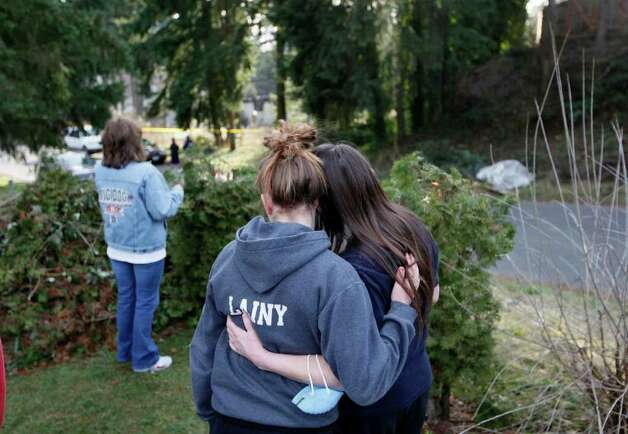 Eliana and her mother Jennifer Bakley hug while Melissa Phillips look over the smoldering remains of a house near Fredrickson, Wash., Sunday, Feb. 5, 2012, where, according to a sheriff's spokesman, three bodies were were found. The bodies are believed to be Josh Powell and his two sons. The explosion occurred moments after a Child Protective Services worker brought the two boys to the home for a supervised visit. Photo: John Froschauer / Associated Press