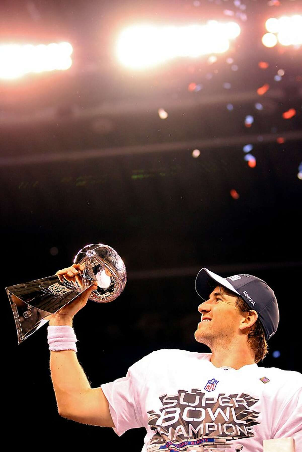 INDIANAPOLIS, IN - FEBRUARY 05: Quarterback Eli Manning #10 of the New York Giants poses with the Vince Lombardi Trophy after the Giants defeated the Patriots by a score of 21-17 in Super Bowl XLVI at Lucas Oil Stadium on February 5, 2012 in Indianapolis, Indiana. (Photo by Ezra Shaw/Getty Images)