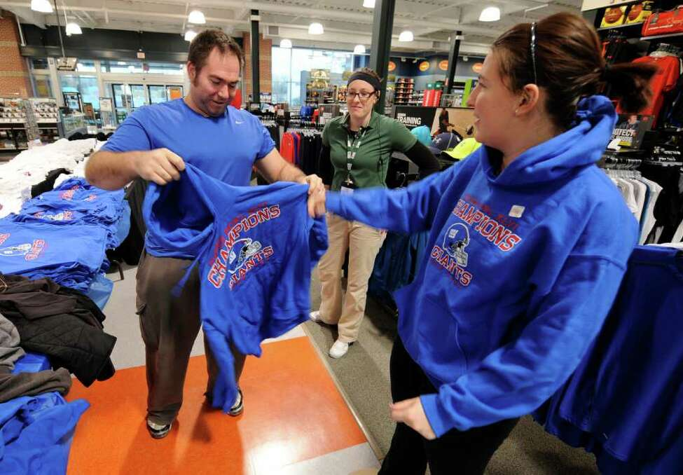 Sarah Streib of Syracuse tries on a New York Giants Super Bowl champions sweatshirt at Dick's Sporting Goods in Crossgates Mall in Guilderland, N.Y., on Monday, Feb 6, 2012. (Skip Dickstein / Times Union)