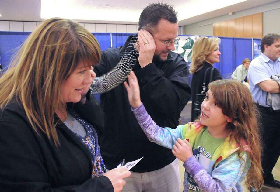 Third grader Kamryn Coates uses her parents, Mishael and Jeff, to perform an sound wave experiment at the Coulson Tough Elementary School booth at the 2012 SCI:// Tech Expo, sponsored by the Education for Tomorrow Alliance, at Lone Star Convention Center in Conroe. 3,000 students participated in the Expo, assisted by 300 volunteers.  David Hopper photograph Photo: David Hopper, For The Chronicle / freelance