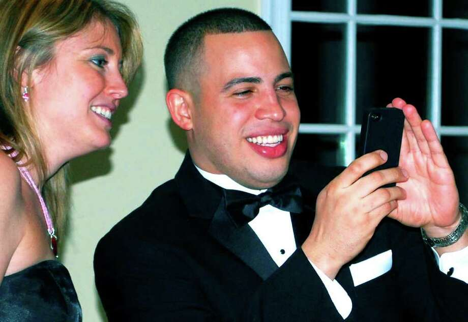 SPECTRUM/Sherry Creighton looks on as her fiancé, Alfredo Calderon of Union Savings Bank in New Milford, snaps a keepsake photo of Jeff Kilberg of Nicholas/Tobin Insurance and his wife, Marina, during the Chamberís 14th annual Crystal Winter Gala, Jan. 28, 2012 at the Candlewood Inn in Brookfield. Photo: Deborah Rose