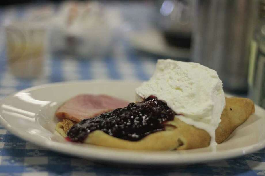 A traditional Swedish pancake is served with lingonberry sauce, whip cream, and a side of ham at the Swedish Cultural Center in Seattle on Sunday. Every month the Swedish Cultural Center hosts a Sunday pancake breakfast that delivers hundreds of Swedish pancakes to over 800 guests. Photo: Sofia Jaramillo / SEATTLEPI.COM