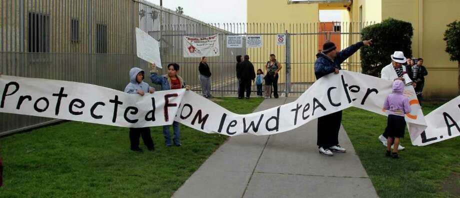 Parents and others protest outside Miramonte Elementary school in Los Angeles on Monday. About three-dozen parents and supporters staged a protest at the Los Angeles-area school rocked by allegations of lewd conduct crimes by two teachers against children. They demanded greater communication with education officials and the placement of cameras in classrooms and hallways at Miramonte Elementary School. Photo: AP