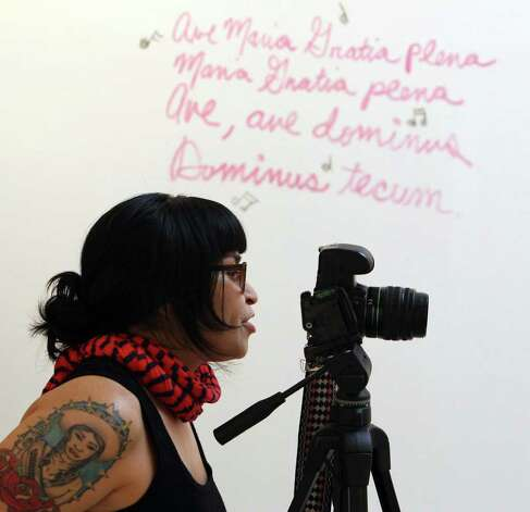 Photographer/artist Mari Hernandez takes pictures at the Guadalupe Gallery for an outdoor installation about motherhood. Photo: Kin Man Hui, San Antonio Express-News / San Antonio Express-News