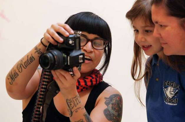 Mari Hernandez (left) shows a photo preview to her subjects, Angelica Olivares and daughter Judy. Photo: Kin Man Hui, San Antonio Express-News / San Antonio Express-News