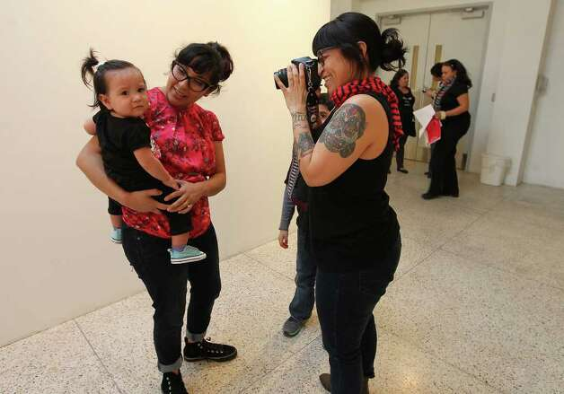Photographer/artist Mari Hernandez (right) makes photographs of Christina Gonzales who was carrying her daughter Eydie at the Guadalupe Gallery for an outdoor installation about motherhood. Photo: Kin Man Hui, San Antonio Express-News / San Antonio Express-News