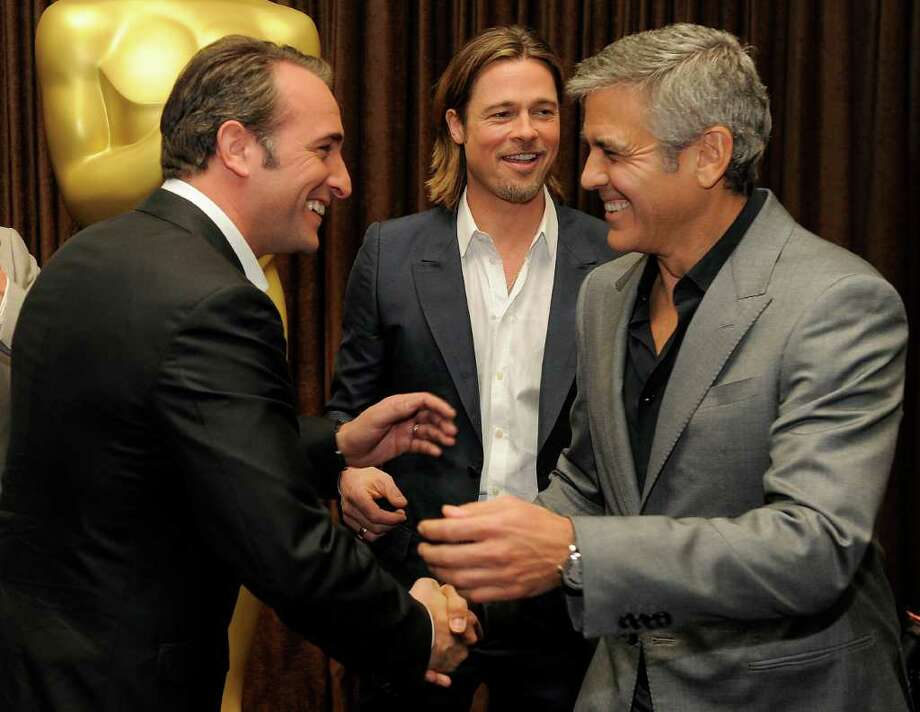 """Academy Awards Best Actor nominees, from left, Jean Jujardin of """"The Artist,"""" Brad Pitt of """"Moneyball"""" and George Clooney of """"The Descendants"""" mingle at the 31st Academy Awards Nominees Luncheon in Beverly Hills, Calif., Monday, Feb. 6, 2012. The 84th Academy Awards will be held in Los Angeles on Sunday, Feb. 26. (AP Photo/Chris Pizzello) Photo: Chris Pizzello"""