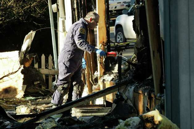A Pierce County fire investigator examines debris, Monday, Feb. 6, 2012, at the home where Josh Powell and his two sons were killed Sunday, in Graham, Wash.. Powell's wife Susan went mysteriously missing from their West Valley City, Utah, home in December 2009. Photo: AP
