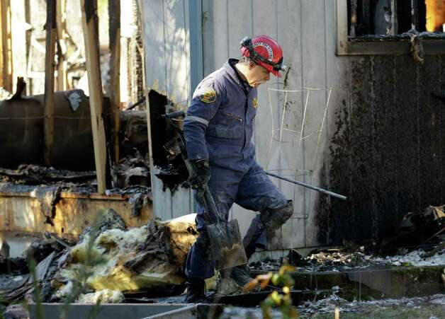A Pierce County fire investigator walks through debris, Monday, Feb. 6, 2012, at the home where Josh Powell and his two sons were killed Sunday, in Graham, Wash., in what police said appeared to be a deliberately set fire. Powell's wife Susan went mysteriously missing from their West Valley City, Utah, home in December 2009. Photo: AP