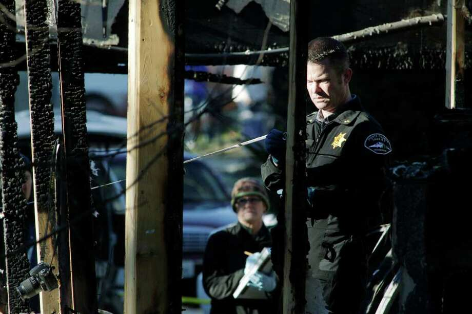 Fire investigators take measurements of charred rubble, Monday, Feb. 6, 2012, at the home where Josh Powell and his two sons were killed Sunday, in Graham, Wash., in what police said appeared to be a deliberately set fire. Powell's wife Susan went mysteriously missing from their West Valley City, Utah, home in December 2009. Photo: AP