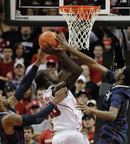 Louisville's Gorgui Dieng, center, attempts a shot through the defensive pressure of Connecticut's Alex Oriakhi, left, and DeAndre Daniels during the first half of their NCAA college basketball game Monday, Feb. 6, 2012 in Louisville, Ky.  (AP Photo/Timothy D. Easley) Photo: Timothy D. Easley, Associated Press / Timothy D. Easley