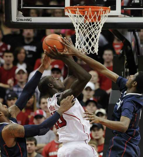 Louisville's Gorgui Dieng, center, attempts a shot through the defensive pressure of Connecticut's A