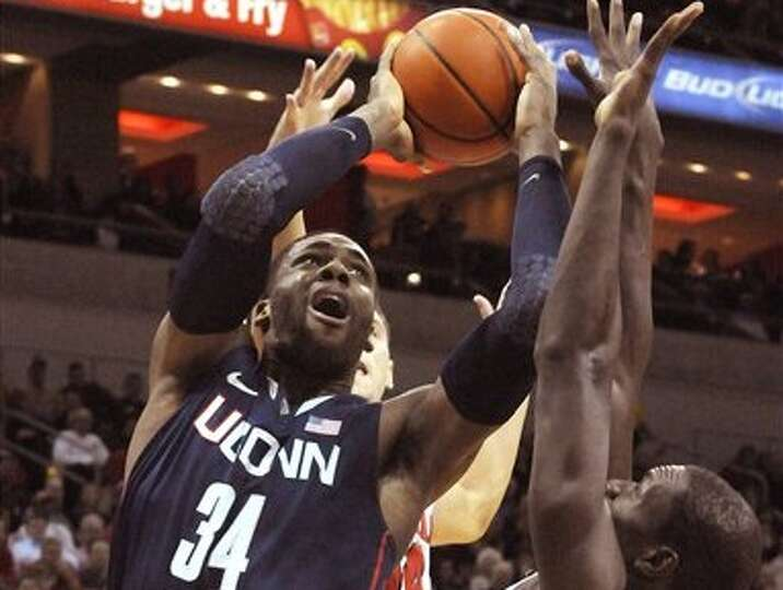Connecticut's Alex Oriakhi, left, puts a shot up over