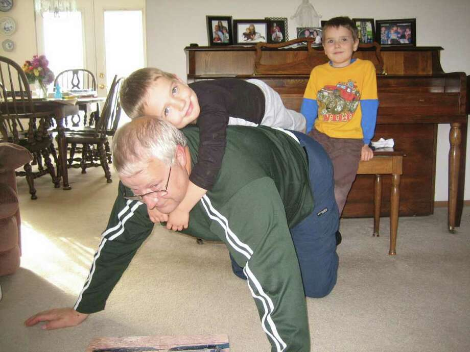 In this undated photo provided by Chuck and Judy Cox, Chuck Cox plays with his grandsons, Charlie, right, and Braden, left. Charlie and Braden were killed along with their father, Josh Powell, on Sunday in what police said was an intentional fire set by Powell. Chuck Cox is the father of Powell's wife, Susan, who has been missing since 2009. (AP Photo/Courtesy Chuck and Judy Cox)