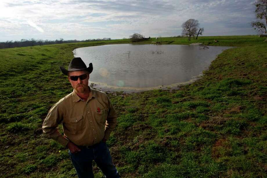 Bo Poole, above, stands next to a much more full pond on his Montgomery ranch on Monday, compared with in June, left, when the pond was nearly dry from drought. Photo: Johnny Hanson, Houston Chronicle / © 2012  Houston Chronicle
