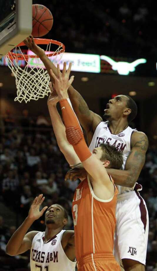 Texas A&M forward David Loubeau (10), top, jumps over Texas forward/center Clint Chapman (53) to tap the ball to a teammate during the first half of a NCAA basketball game, Monday, Feb. 6, 2012, in Reed Arena in College Station Photo: Nick De La Torre, Houston Chronicle / © 2012  Houston Chronicle
