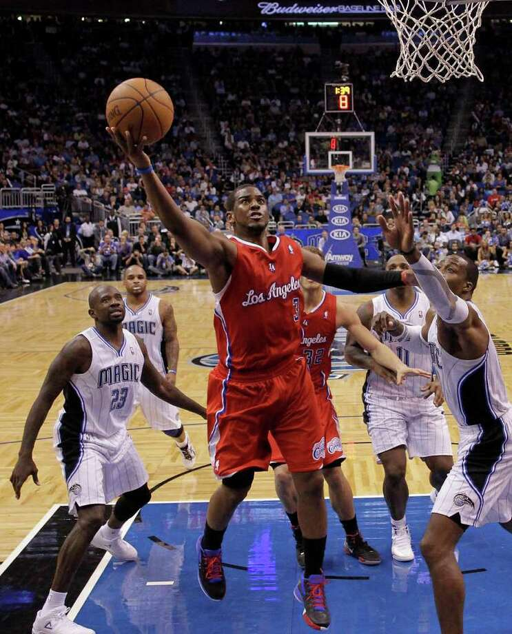 Los Angeles Clippers' Chris Paul (3) drives to the basket between Orlando Magic's Jason Richardson (23) and Dwight Howard, right, during the second half of an NBA basketball game Monday, Feb. 6, 2012, in Orlando, Fla. The Clippers won 107-102 in overtime. Photo: AP