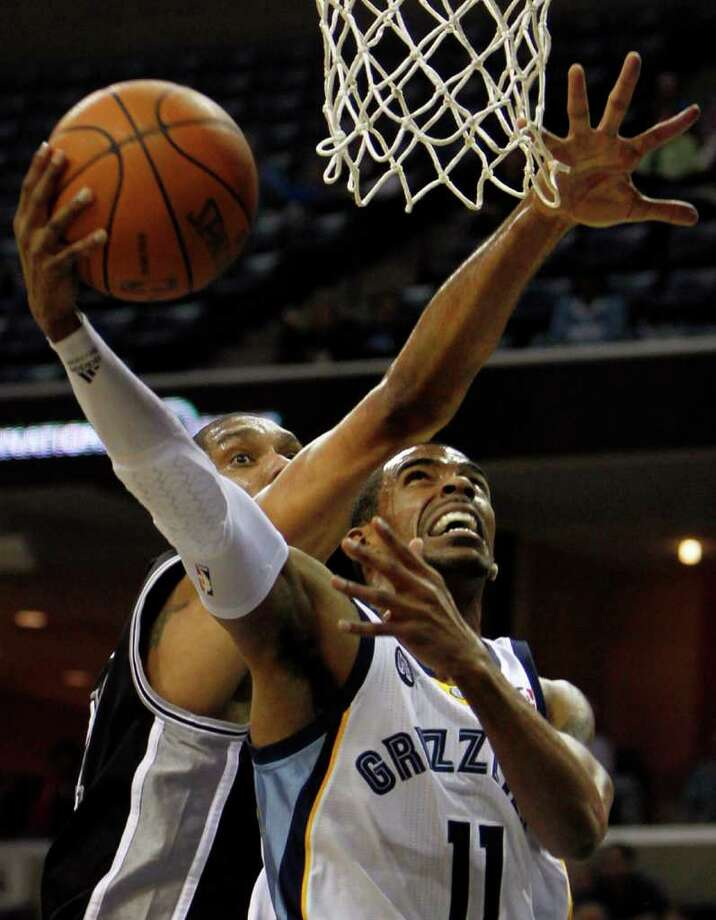 Memphis Grizzlies guard Mike Conley (11) shoots under pressure by San Antonio Spurs forward Tim Duncan,  left, in the first half of an NBA basketball game on Monday, Feb. 6, 2012, in Memphis, Tenn. Photo: AP