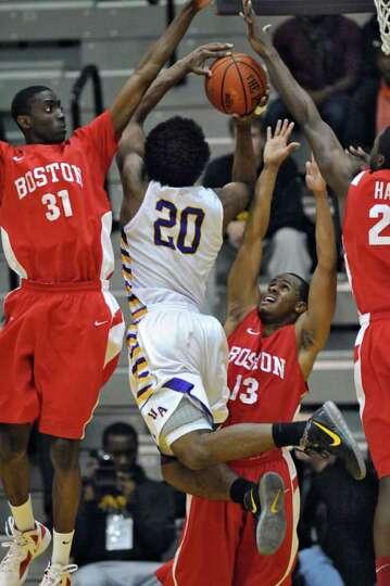 UAlbany's Gerardo Suero drives to the basket while Boston University's Malik Thomas, left, and D. J.