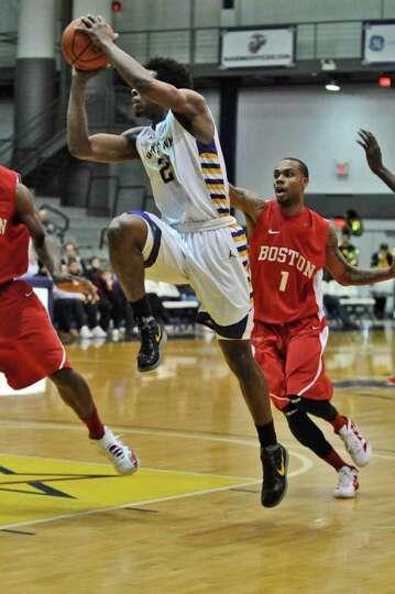 UAlbany's Gerardo Suero drives to the basket while Boston University's Darryl Partin defends, during