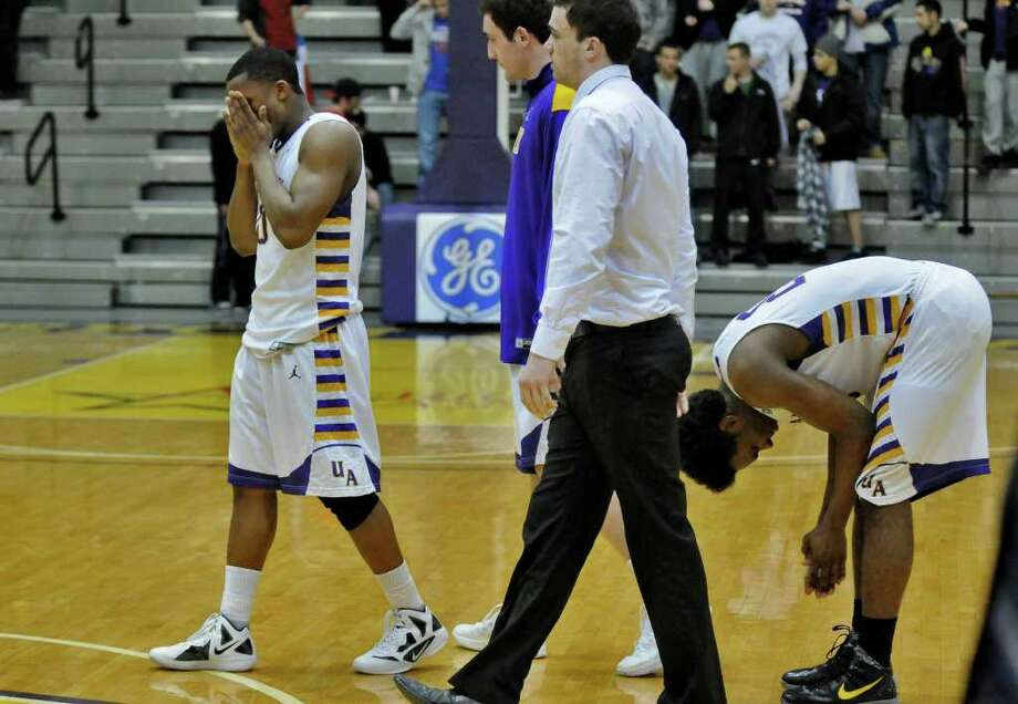 UAlbany's Mike Black, left, and Gerardo Suero, right, and  teammates Sam Rowley, second from left, and Peter Hooley, second from right,  are dejected moments after the end of UAlbany's 81-78 loss to Boston University at the SEFCU Arena on Monday night Feb. 6, 2012 in Albany, NY.  UAlbany was leading by 17 points late in the first half.  (Philip Kamrass / Times Union ) Photo: Philip Kamrass / 00016316A