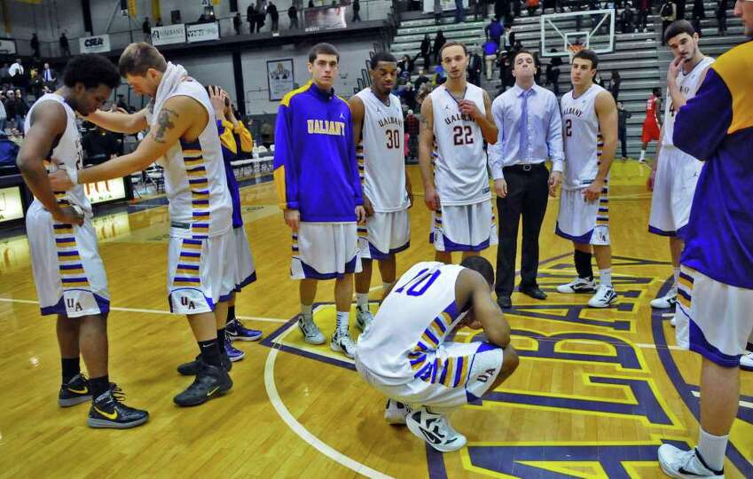 UAlbany's Gerardo Suero, left, is comforted by teammate Blake Metcalf, second from left, as they gat