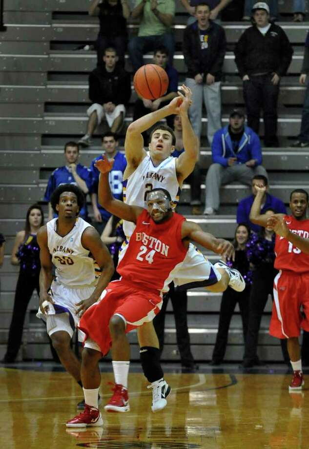 UAlbany's Gerardo Suero, left, and Logan Aronhalt, right, battle with Boston University's Travis Robinson for a ball late in the second half of UAlbany's 81-78 loss at the SEFCU Arena on Monday night Feb. 6, 2012 in Albany, NY.  M UAlbany was leading by 17  at one point late in the first half.  (Philip Kamrass / Times Union ) Photo: Philip Kamrass / 00016316A