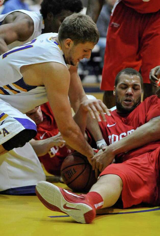 UAlbany's Blake Metcalf battles for a loose ball with Boston University's Dom Morris during the second half of UAlbany's 81-78 loss at the SEFCU Arena on Monday night Feb. 6, 2012 in Albany, NY.  M UAlbany was leading by 17  at one point late in the first half.  (Philip Kamrass / Times Union ) Photo: Philip Kamrass / 00016316A