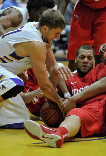 UAlbany's Blake Metcalf battles for a loose ball with Boston University's Dom Morris during the seco