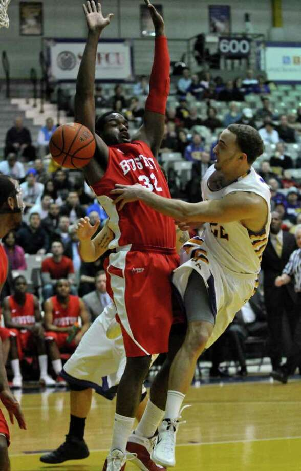 UAlbany's Ralph Watts passes the ball while defended by Boston University's Jeff Pelage during the first half of UAlbany's 81-78 loss to Boston University at the SEFCU Arena on Monday night Feb. 6, 2012 in Albany, NY.   UAlbany was leading by 17  at one point late in the first half.  (Philip Kamrass / Times Union ) Photo: Philip Kamrass / 00016316A