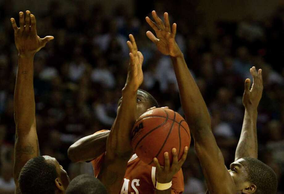 Texas guard J'Covan Brown (14) looks for an opening in a forrest of Texas A&M defenders arms during the second half of a NCAA basketball game, Monday, Feb. 6, 2012, in Reed Arena in College Station. Texas won 70-68. Photo: Nick De La Torre, Houston Chronicle / © 2012  Houston Chronicle