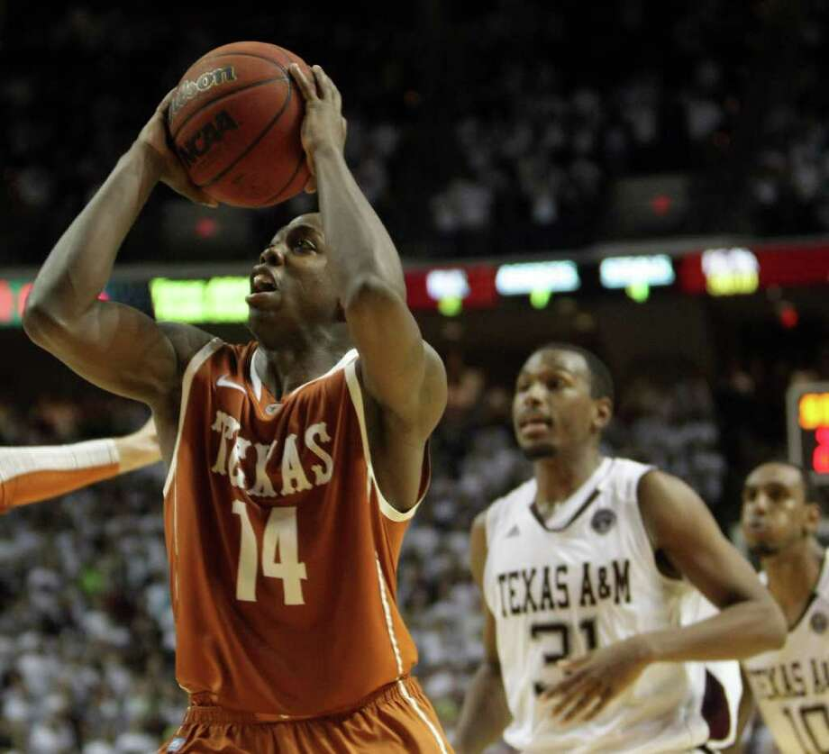 Texas guard J'Covan Brown (14) drives past two Texas A&M defenders for a layup during the second half of a NCAA basketball game, Monday, Feb. 6, 2012, in Reed Arena in College Station. Texas won 70-68. Photo: Nick De La Torre, Houston Chronicle / © 2012  Houston Chronicle
