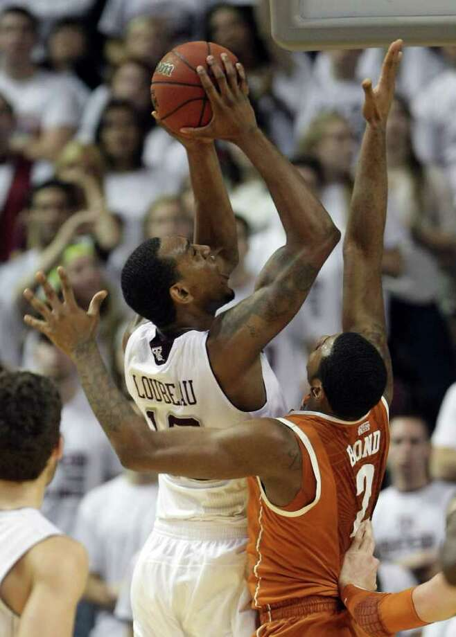 Texas A&M forward David Loubeau (10) works hard to get the past Texas forward Jaylen Bond (2) during the second half of a NCAA basketball game, Monday, Feb. 6, 2012, in Reed Arena in College Station. Texas won 70-68. Photo: Nick De La Torre, Houston Chronicle / © 2012  Houston Chronicle