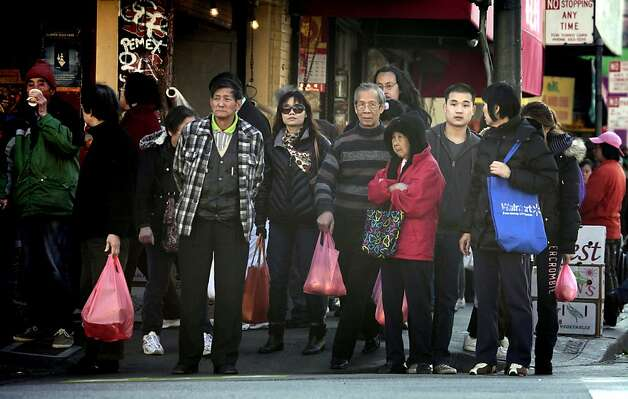 San Francisco China Town shoppers fill their bags as they roam through the business district Tuesday December 6, 2011. San Francisco Board of Supervisors voted Tuesday on whether to make stores and restaurants start charging customers 10 cents for every bag handed out at the checkout counter. Exceptions will be made for frozen food, meat and fish, flowers and plants, unwrapped prepared foods or bakery goods. Otherwise, bags for everything else, from a carton of milk to a paperback book, will start costing. Photo: Lance Iversen, The Chronicle