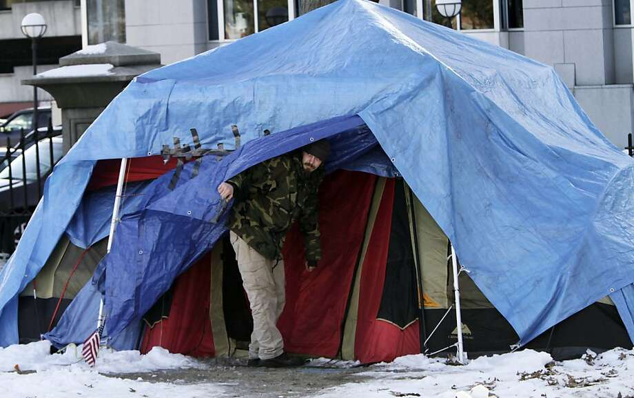 A man looks out from one of the few remaining tents at the Occupy Maine encampment in Lincoln Park in Portland, Maine, on Monday, Feb. 6, 2012.  A deadline for Occupy Maine to dismantle its encampment came and went Monday morning with no action by police, and several tents remained in Lincoln Park.  (AP Photo/Pat Wellenbach) Photo: Pat Wellenbach, Associated Press