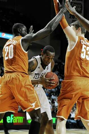 Texas A&M's David Loubeau, center, is double-teamed by Texas defenders Alexis Wangmene (20) and Clint Chapman (53) in the first half of an NCAA college basketball game Monday, Feb. 6, 2012, in College Station, Texas. (AP Photo/Pat Sullivan) Photo: Pat Sullivan, Associated Press / AP