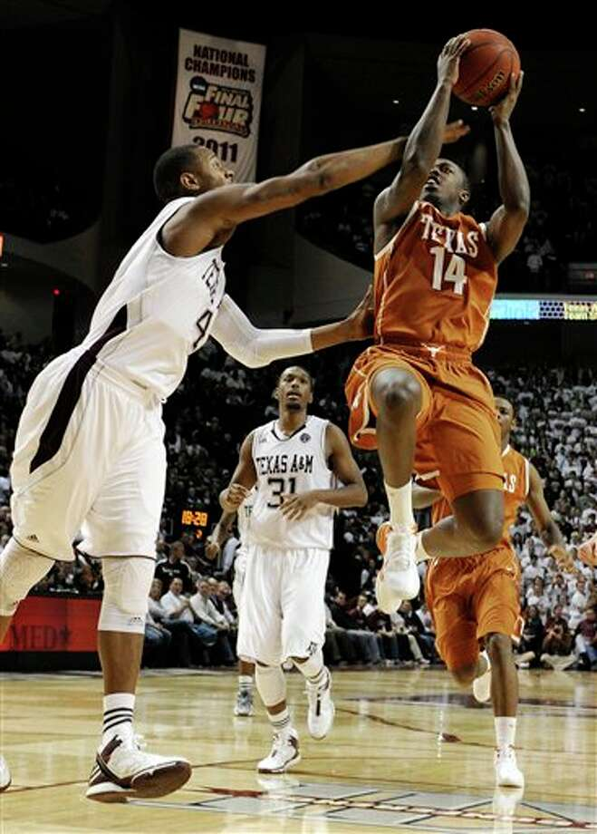 Texas' J'Covan Brown (14) goes to the basket while guarded by Texas A&M's Keith Davis (4) in the second half of an NCAA college basketball game Monday, Feb. 6, 2012, in College Station, Texas. (AP Photo/Pat Sullivan) Photo: Pat Sullivan, Associated Press / AP2012