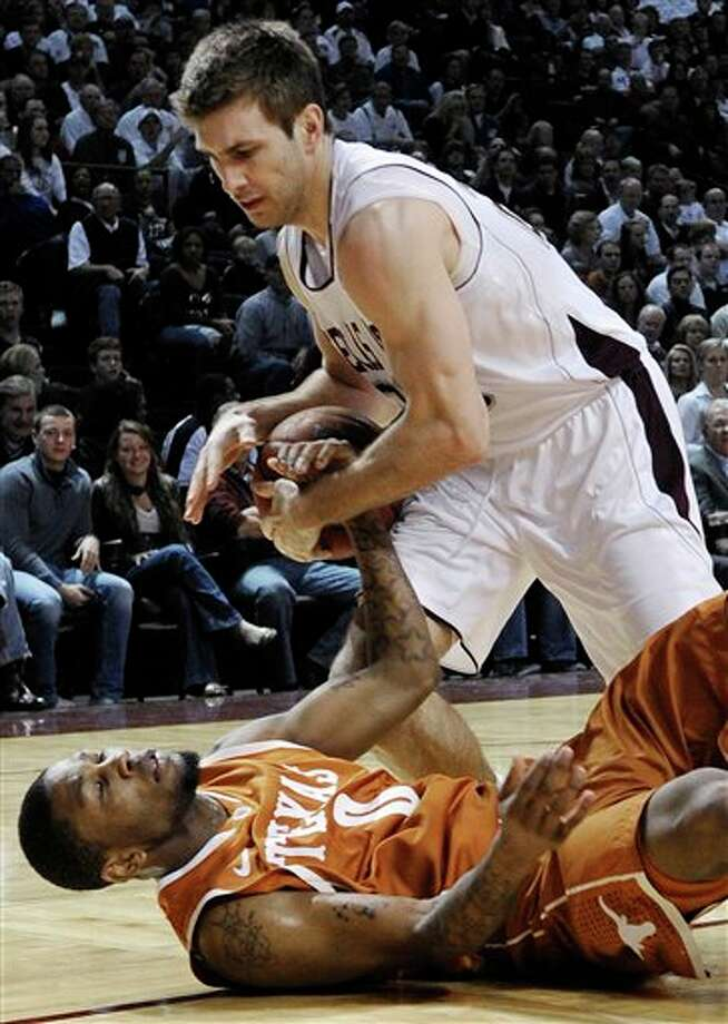 Texas' Julien Lewis (0) and Texas A&M's Zach Kinsley fight for the ball in the second half of an NCAA college basketball game Monday, Feb. 6, 2012, in College Station, Texas. Texas won 70-68. (AP Photo/Pat Sullivan) Photo: Pat Sullivan, Associated Press / AP