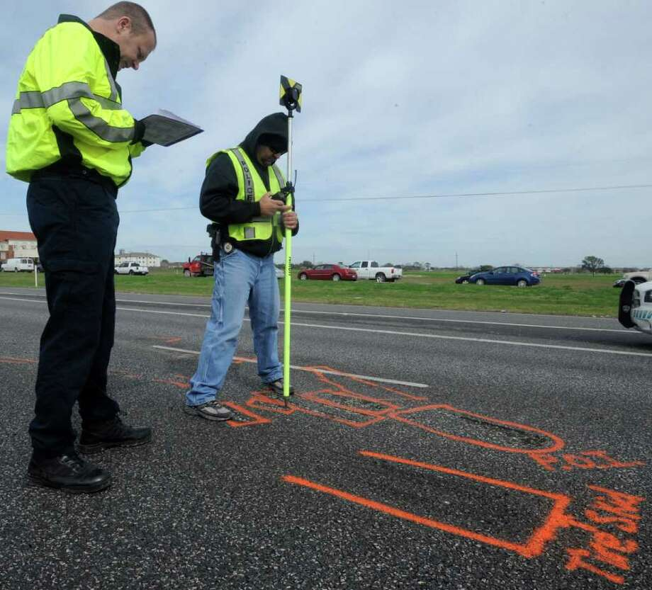 Officer Tim Dinger, left,  records the point that officer Larry Myers, right,  was lining  up with the prism. The Port Arthur police department blocked off a portion of northbound US 69 Monday morning to recreate the wreck from January 27 when a woman slammed on her breaks in front of a truck and caused another vehicle to hit the truck. The driver of the other vehicle died several days later from his injuries.    Dave Ryan/The Enterprise