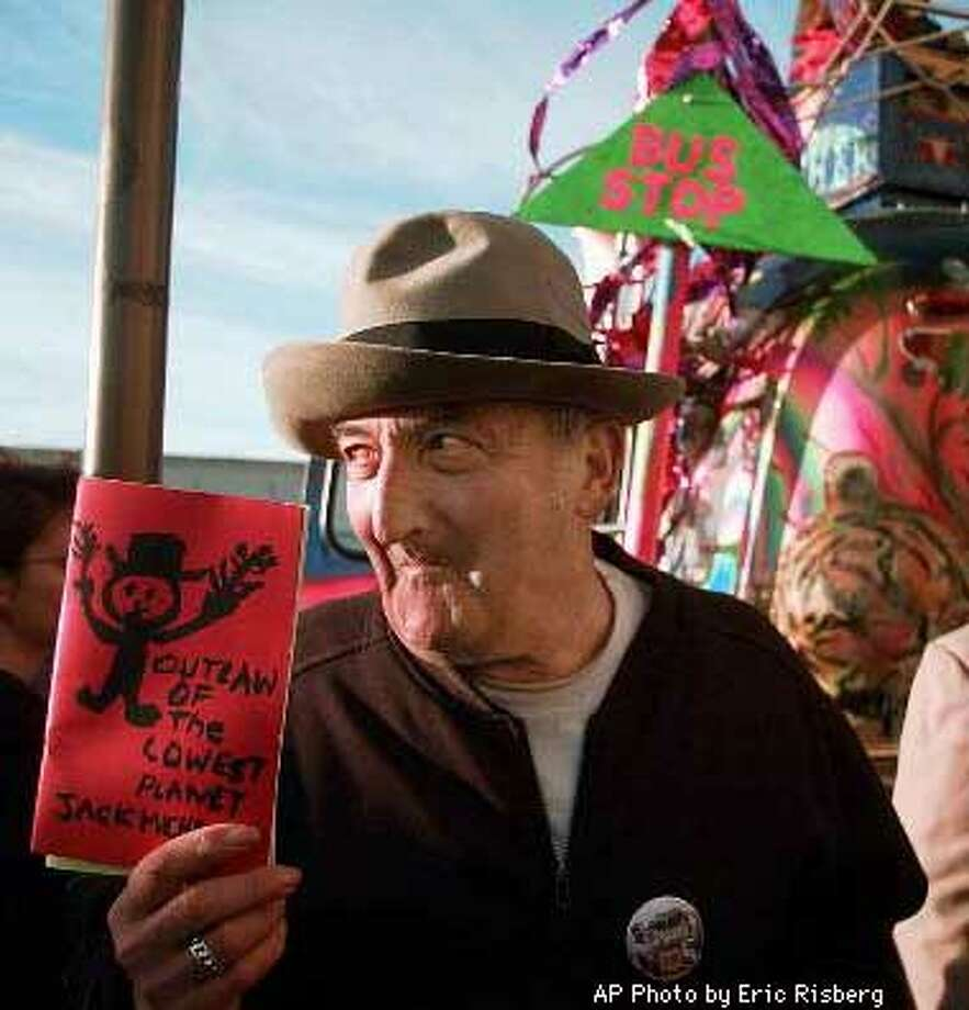 "Beat poet Jack Micheline of San Francisco, shows off some of his published work to those attending the psychedelic-era reunion party at the historic Fillmore Auditorium in San Francisco, Monday April 28, 1997. In the background is the bus Furthur. The party celebrates an upcoming exhibit this summer at the Rock and Roll Hall of Fame in Cleveland on the 30th anniversary of the ""Summer of Love."" AP Photo by Eric Risberg"