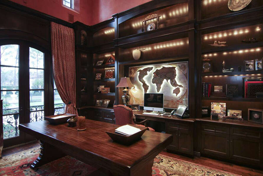 The study is filled with built-in book shelves and cabinetry.