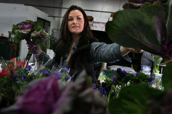 Eco-minded florist Christina Stembel of Farmgirl Flowers sourcing her flowers at the San Francisco Flower Mart in San Francisco, Calif., while looking at purple kale on Thursday, February 2, 2012.  She sources  locally grown flowers and plants.