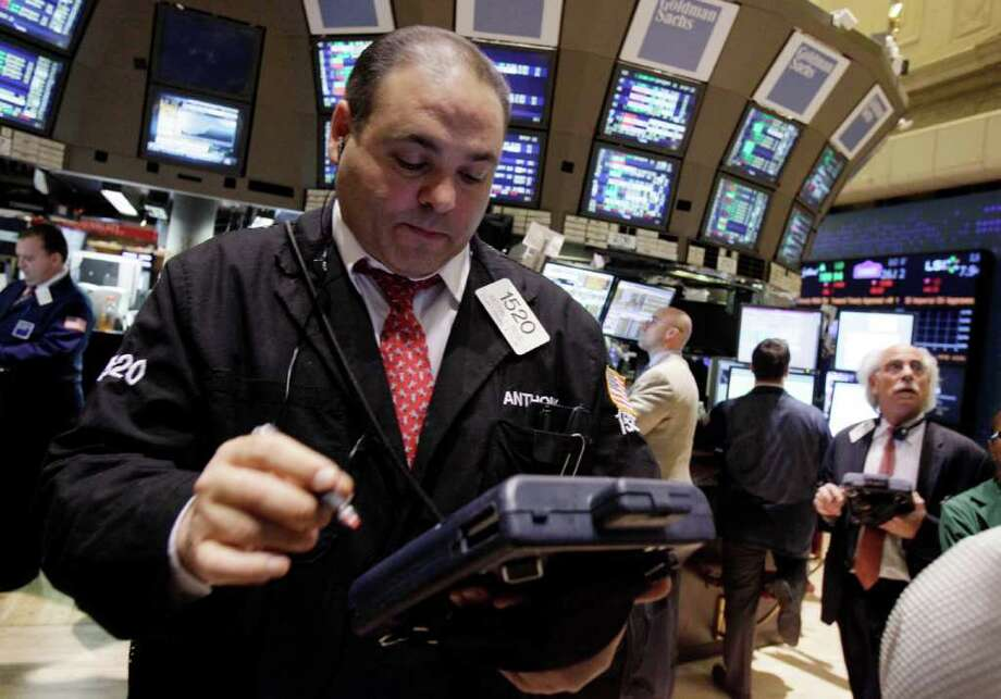 In this Feb. 3, 2012 photo, trader Anthony Riccio, left, works on the floor of the New York Stock Exchange. Stocks were trading lower on Tuesday, Feb. 7,2012, as talks dragged on in Greece to agree the terms of a second bailout _ and avoid looming bankruptcy _ despite intense pressure from the country's euro partners. (AP Photo/Richard Drew) Photo: Richard Drew / AP