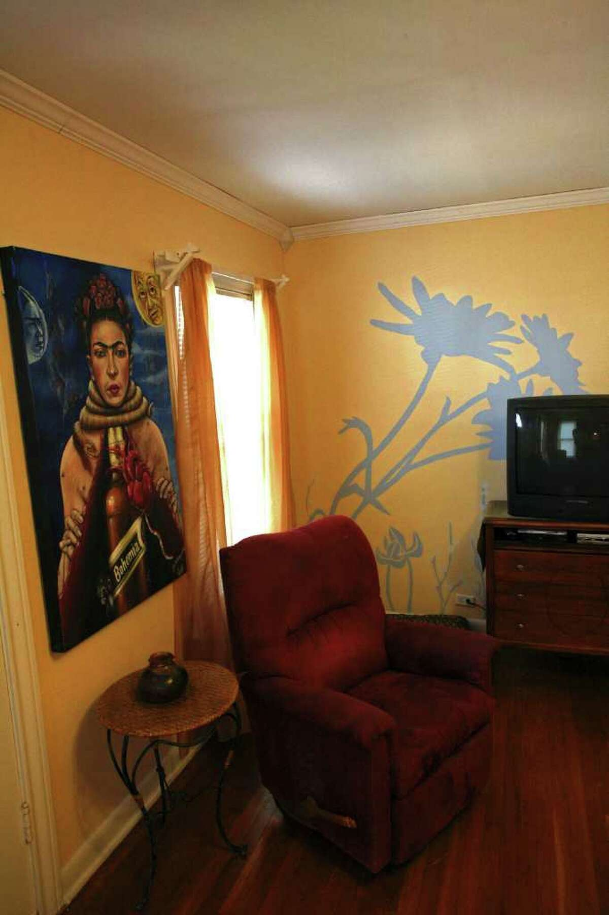 A painting by Jose Guajardo dominates one wall in the living room; Sarah Shore painted the large blue and white flowers on another wall.