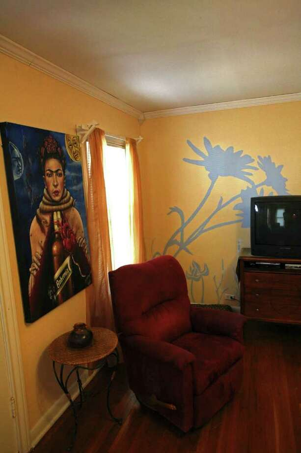 A painting by Jose Guajardo dominates one wall in the living room; Sarah Shore painted the large blue and white flowers on another wall. Photo: DANNY WARNER