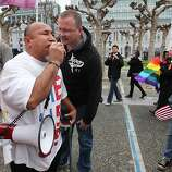 Solonua Solonua, left, is confronted by a same-sex activist, while he preaches at couples as they walk towards City Hall, Tuesday February 7, 2012, to celebrate the 9th U.S. Circuit Court of Appeals ruling that Proposition 8 in unconstitutional, in San Francisco, Calif.