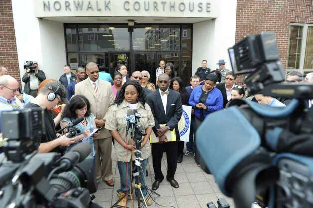 Tanya McDowell speaks reporters, with Jack Bryant of the Stamford NAACP, left, and attorney Darnell Crosland, right, before her arraignment in state Superior Court in Norwalk Wednesday on larceny charges. McDowell allegedly used a false Norwalk address to enroll her son in school. Photo: Kathleen O'Rourke, ST / Stamford Advocate