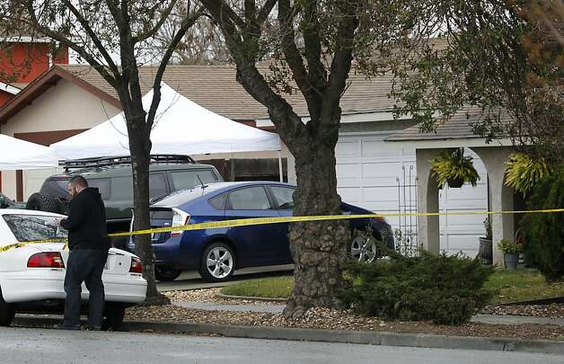 Police investigators gather evidence at the scene following a shooting which wounded a federal officer in front of his home (right) in Newark, Calif. on Tuesday, Feb. 7, 2012. Photo: Paul Chinn, The Chronicle